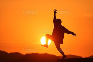 夕日の前で空を飛ぶ人の写真・画像素材[2857071]