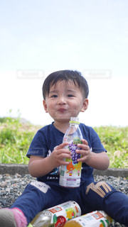ピクニックテーブルに座っている小さな男の子の写真・画像素材[2214540]