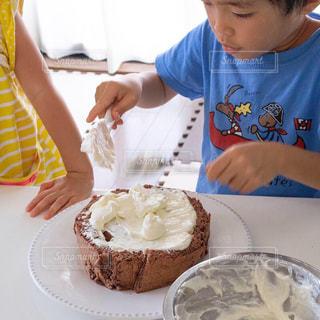 皿の上でケーキを切る少年の写真・画像素材[2703488]