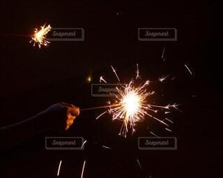 夏,夜,花火,手,手持ち,人物,ポートレート,明るい,思い出,ライフスタイル,夏の終わり,夏祭り,手元,輝き,手持ち花火,パチパチ,ピカッ