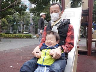 滑り台で遊んでる花粉症の父と楽しい息子の写真・画像素材[1074267]