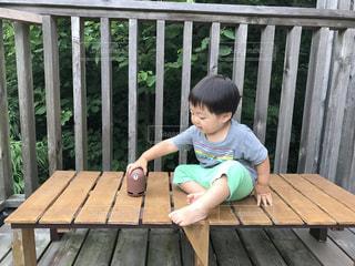 木製のベンチに座っている少年の写真・画像素材[1358240]