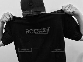 黒いシャツを持った男の写真・画像素材[2105044]