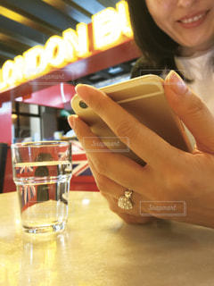 テーブルでスマホを見る女性の写真・画像素材[2283768]