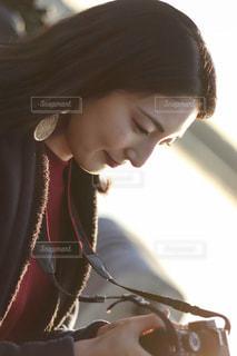 日差しに包まれるカメラ女子の写真・画像素材[1871709]