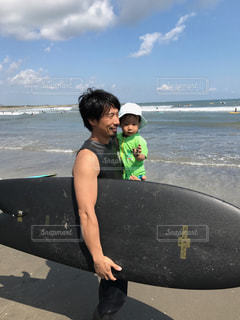 サーフィン ボードを持ってビーチに立っている少年の写真・画像素材[952223]
