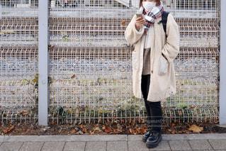 フェンスの前に立っている人の写真・画像素材[2857369]