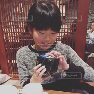 食べ物を食べながらテーブルに座っている小さな男の子の写真・画像素材[2340816]