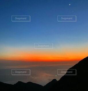 山を背景にした水の体に沈む夕日の写真・画像素材[3394634]
