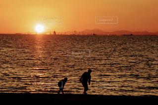バック グラウンドで夕焼けのビーチに立っている人の写真・画像素材[960701]