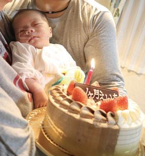誕生日ケーキの前で座っている赤ちゃんの写真・画像素材[1667538]