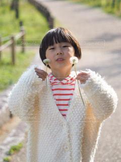 フェンスの隣に立っている小さな女の子の写真・画像素材[2279994]
