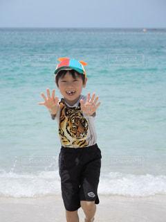 海の隣の砂浜の上に乗っている人の写真・画像素材[2330924]