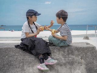 浜辺に座っている少年の写真・画像素材[2330925]