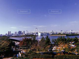 バック グラウンドで市と水の体の上の橋の写真・画像素材[1904065]
