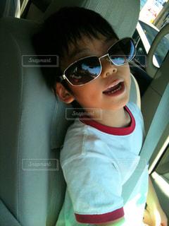 サングラスをかけて車に座る少年の写真・画像素材[2105729]