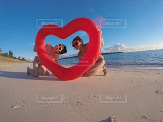 女性,海,空,夕日,屋外,太陽,赤,砂,サングラス,ビーチ,砂浜,水着,水面,ハート,人,浮き輪,景観