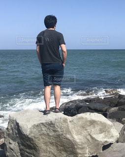 男性,30代,海,夏,屋外,後ろ姿,岩,人物,背中,人,後姿,Tシャツ,白波,短パン