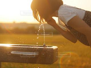 女性,夏,屋外,水,夕焼け,水飲み場,水滴,夕方,キラキラ,水玉,河川敷,風,飛沫,夕陽,雫,午後,玉ボケ,しずく,オールドレンズ