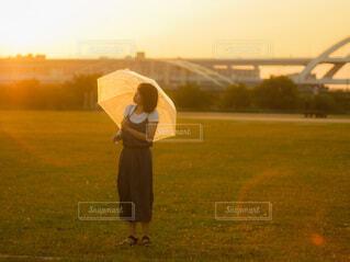 野原に立ちながら凧を持っている人の写真・画像素材[3670338]