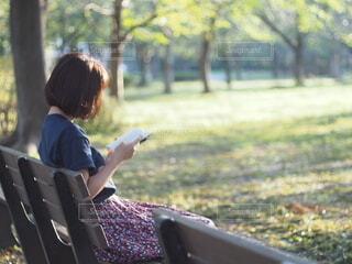 公園のベンチに座って、ラップトップを見ている人の写真・画像素材[3690331]