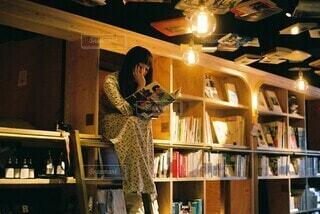 本棚の前に立っている人の写真・画像素材[3690352]