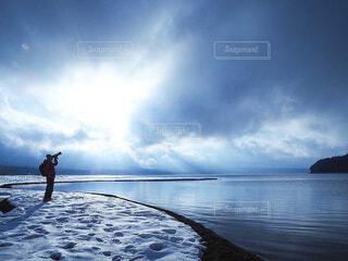水の体の隣に立っている人の写真・画像素材[4136971]