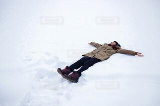 雪に覆われた斜面の下にスノーボードに乗っている人の写真・画像素材[4136972]