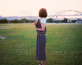 芝生で覆われた畑の上に立っている人の写真・画像素材[4528954]