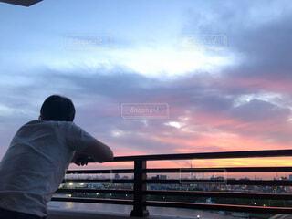 日没前のベンチに座っている男の写真・画像素材[4533519]