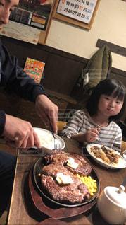 食べ物のあるテーブルに座っている人々のグループの写真・画像素材[2225048]