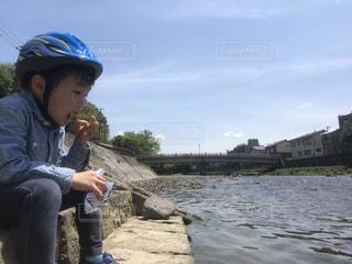 川辺に座っている小さな男の子の写真・画像素材[2090115]