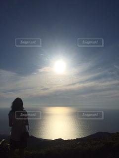 海,夕日,後ろ姿,背中,夕日と女性