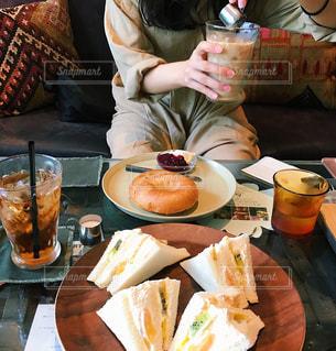 食べ物の皿を持ってテーブルに座っている女性の写真・画像素材[2259153]