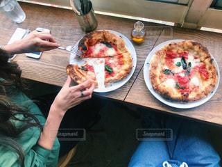 ピザを食べるテーブルに座っている人の写真・画像素材[2259272]