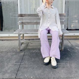 携帯電話で話しているベンチに座っている人の写真・画像素材[3110179]