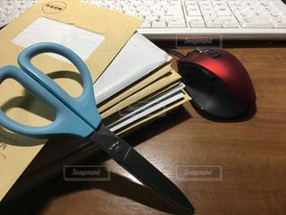 木製の机の上にあるたくさんの封筒とハサミ、マウスとキーボードの写真・画像素材[2782601]