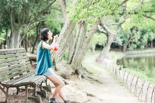 公園のベンチに座ってかき氷を食べる女性の写真・画像素材[3578291]