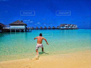 浜辺でフリスビーを投げる男の写真・画像素材[2107639]