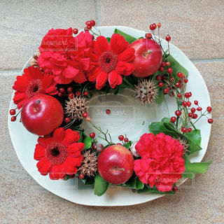赤い花と白いプレートの写真・画像素材[1933372]