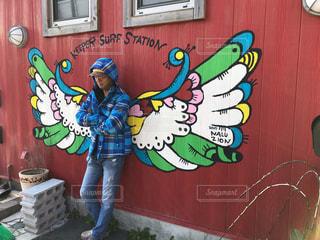 天使の羽が絵ががれた壁の前に立っている人の写真・画像素材[2121609]