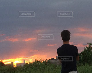 夕焼けを眺めている男の写真・画像素材[2420560]