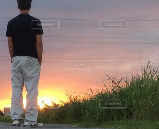 夕焼けの前に立っている男の写真・画像素材[2420566]
