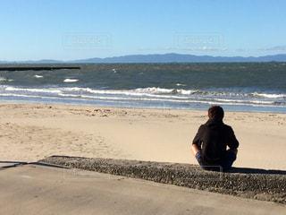 波を見て癒されている男の写真・画像素材[2606497]