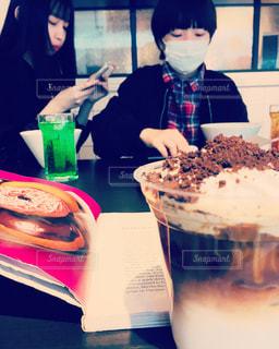 コーヒーを飲みながらテーブルに座っている人の写真・画像素材[2277728]