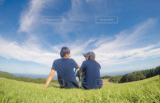芝生の丘の上に立っている男の写真・画像素材[2109337]