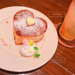 テーブルの上に置くチョコレートケーキをトッピングした白い皿の写真・画像素材[2264064]