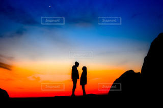 夕焼けの前に立っている男の写真・画像素材[2271825]