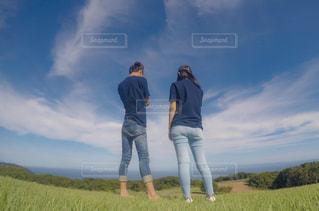 草の生いた丘の上に立っている人の写真・画像素材[2416639]