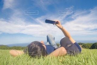 野原に座っている人の写真・画像素材[3878353]